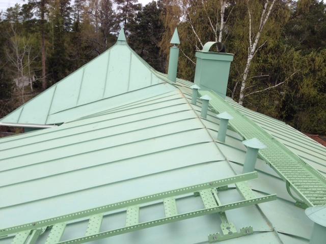 Bandtäckning i ärggrön plåt, med färganpassade takskyddsanordningar